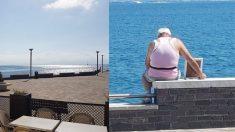 L'anziano osserva il mare, abbracciando la foto della moglie defunta