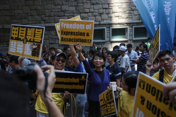 I manifestanti marciano durante una manifestazione contro l'articolo 23 a Hong Kong