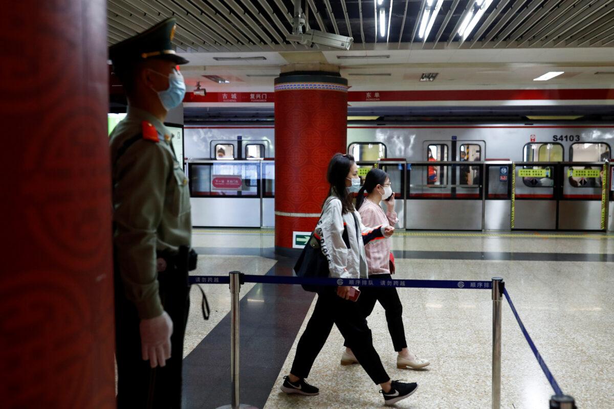 Un agente di polizia paramilitare sorveglia una stazione della linea uno della metropolitana che passa davanti alla Sala Grande del Popolo, sede del prossimo Congresso Nazionale del Popolo (Npc) a Pechino, Cina 19 maggio 2020. (Thomas Peter/Reuters)