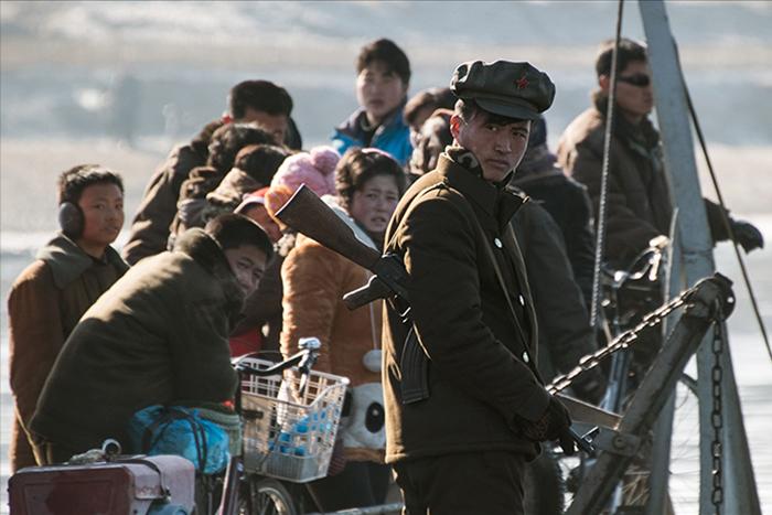9 Febbraio 2016: Un soldato nord-coreano di guardia su un'imbarcazione con abitanti del posto, mentre naviga sul fiume Yalu, che separa la città nordcoreana di Sinuiju da quella cinese di Dandong (Johannes Eisele/Afp/Getty Image).